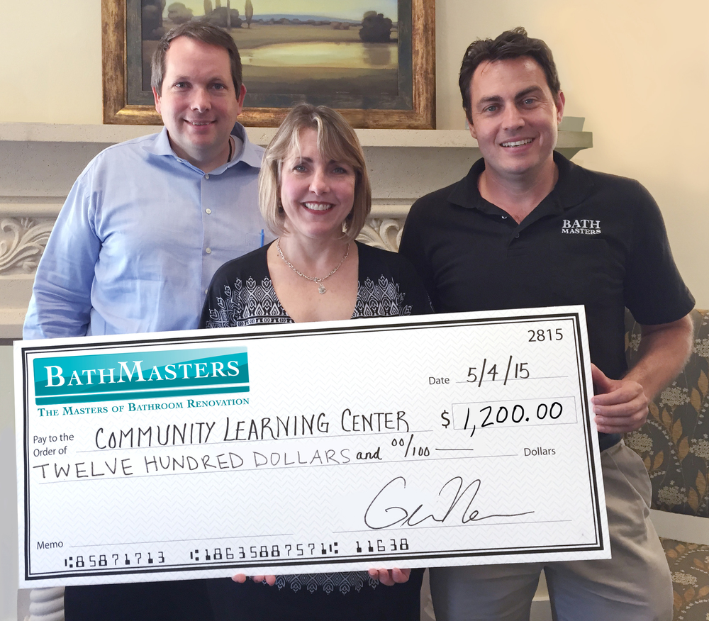 Greg and Aaron giving a check to Holly Haggerty, Executive Director of The Community Learning Center