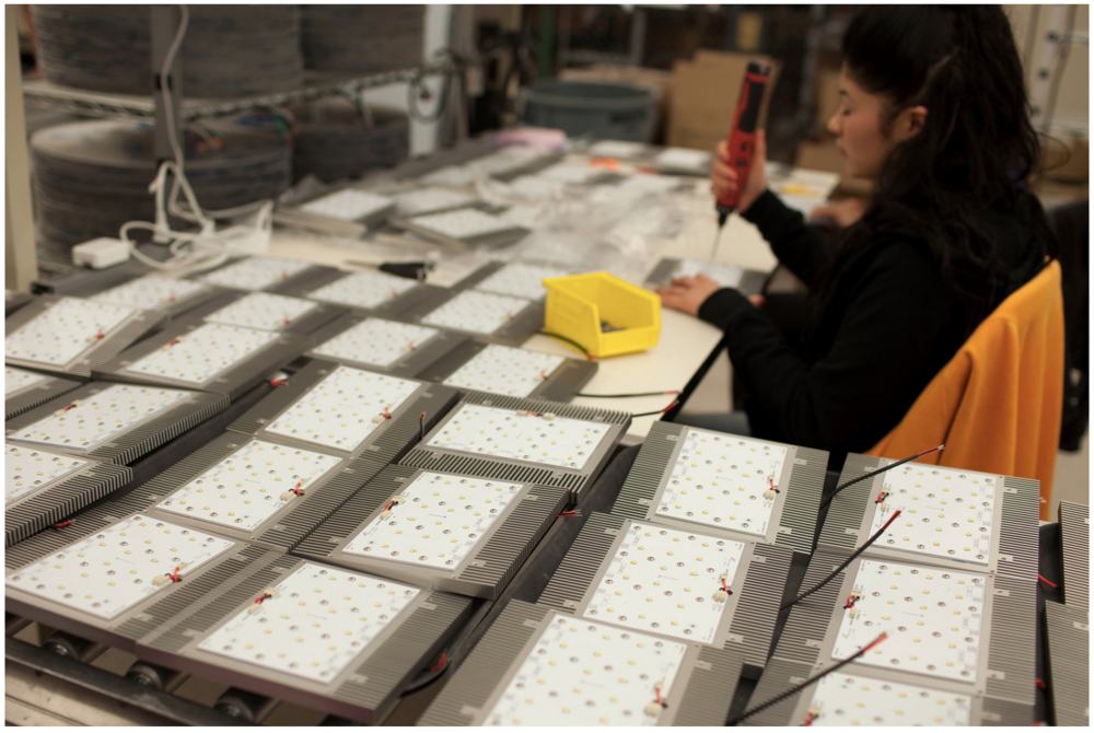 An assembler at Sensity Systems works on one of the company's sensor-equipped, wirelessly networked lighting fixtures. Credit Peter DaSilva for The New York Times
