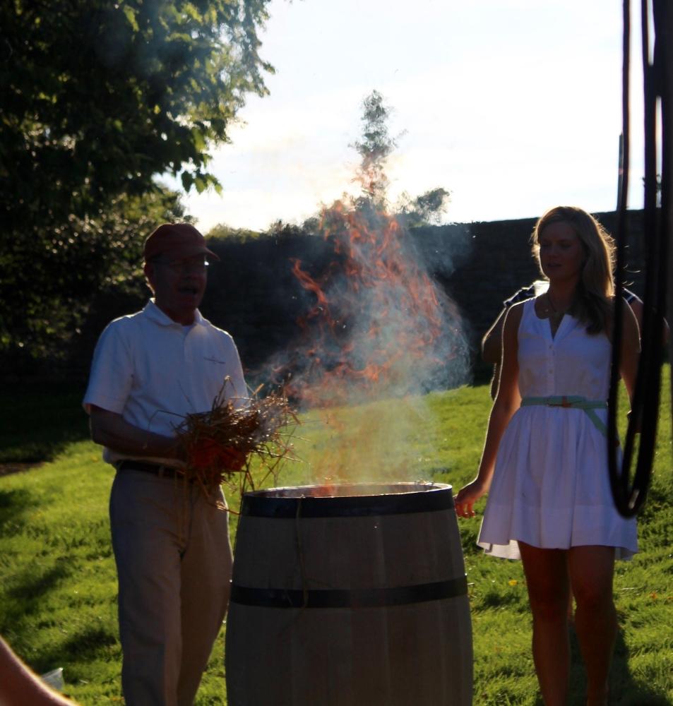 Woodford Reserve Master Distiller Chris Morris and Master Taster Elizabeth O'Neill char a bourbon barrel.