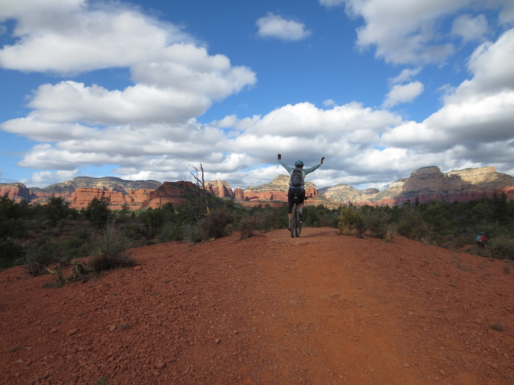 Sandhya flies into the Sedona sky along a rare patch of smooth, wide trail.