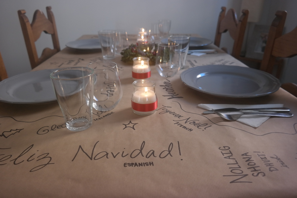 "Our Christmas dinner table. Covering our table in brown paper and writing ""Merry Christmas"" in different languages is a very cheap way to decorate and a super easy way to clean up quickly!"