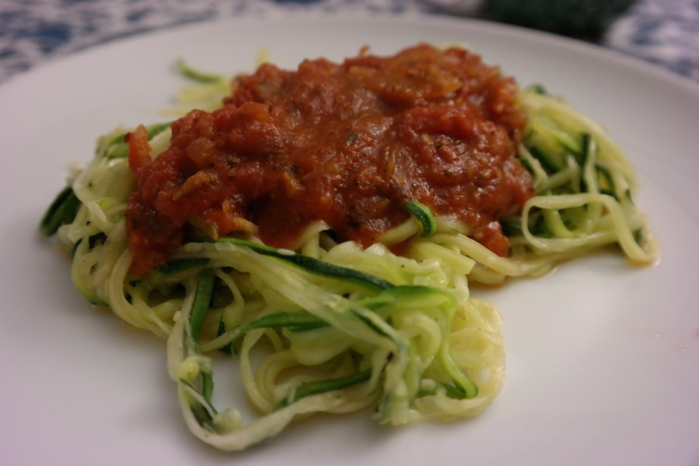 "Zucchini noodles with pasta sauce. This recipe was John's idea, and after he ordered a special ""noodle"" cutter on Amazon, he made a homemade pasta sauce to go along with the zucchini ""noodles."" I loved it!"