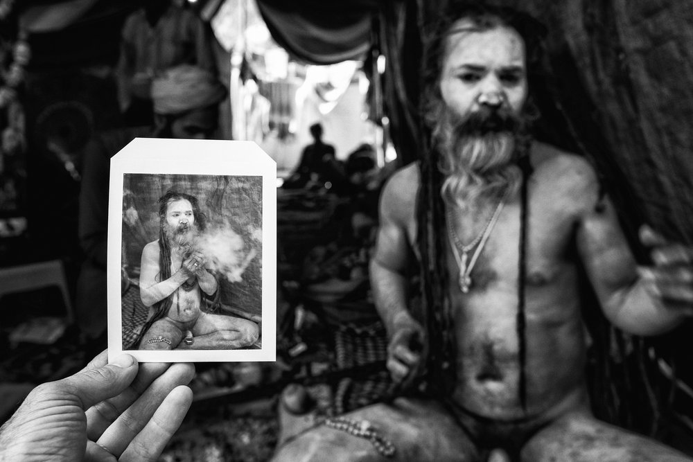 A picture from the archives. Photo taken in Haridwar, India at the Kumbh Mela. I met up with Stephen Dupont who was also documenting the festival. Stephen is reviewing a polaroid before he sets up his white sheet.    © Russell Shakespeare