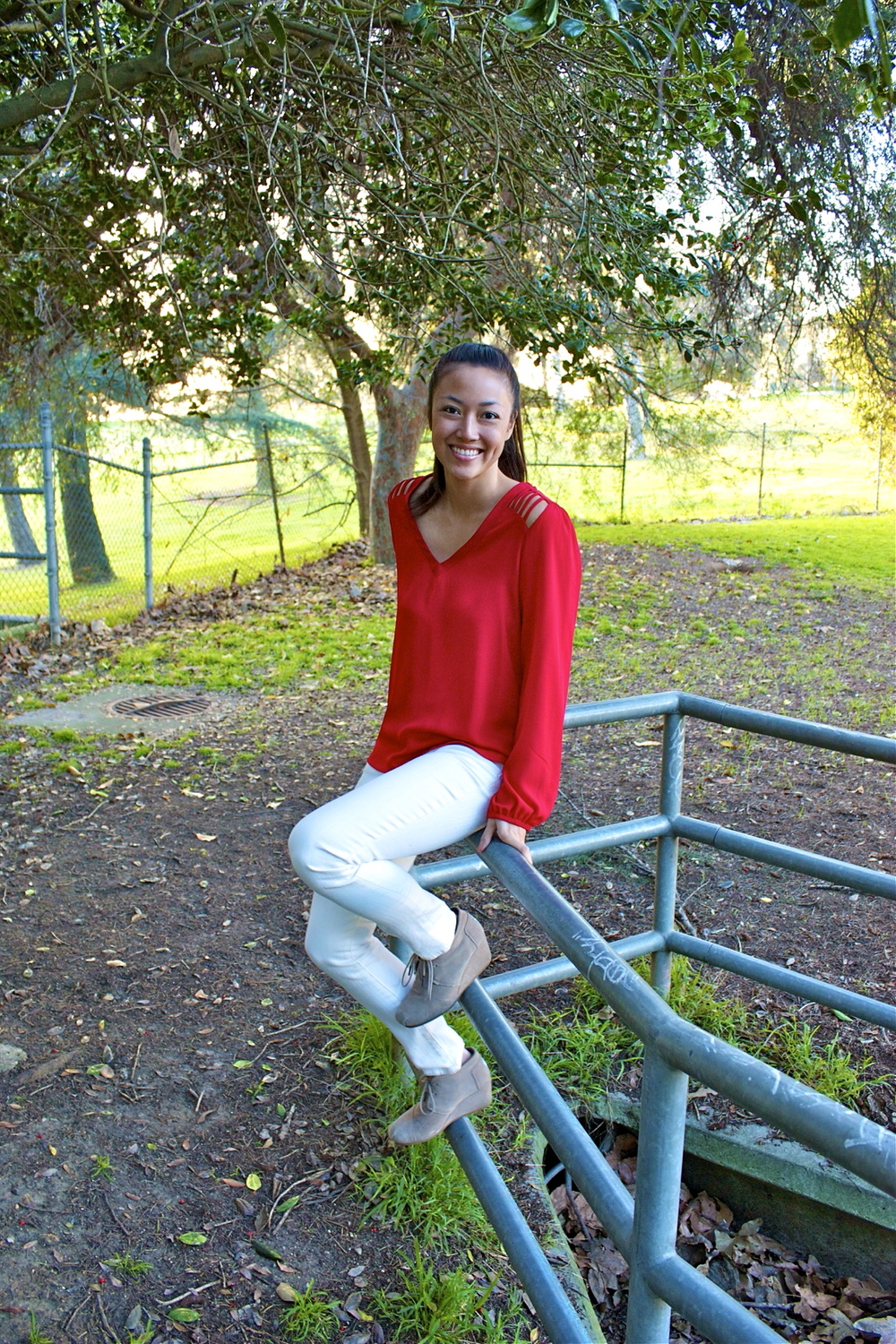 red shirt white jeans sitting on railing