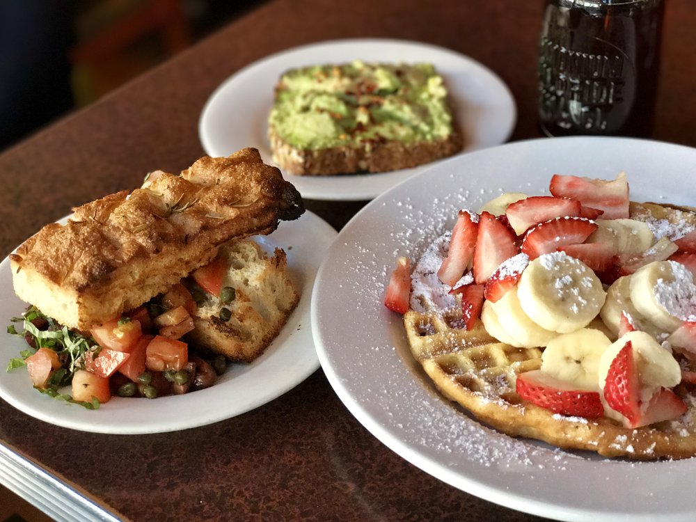 Baked Focaccia with tomatoes and capers. Orange blossom waffle with fruit and maple syrup.