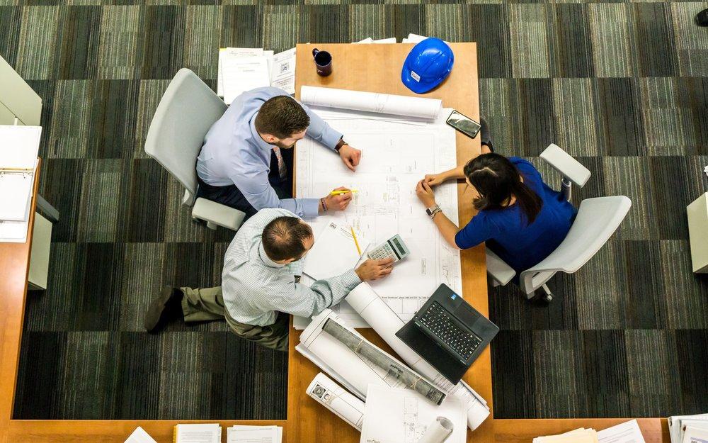 laptop i ljudi za uredskim stolom s nacrtima i kalkulatorom.jpg