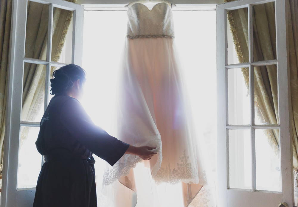 Is this photo technically correct? No way! But I am so in love with it. I love capturing the moment a bride is about to put on her dress!Up to this point, all she's ever done is try it on. Today, she put's it on knowing that in a few short moments she'll be a Mrs. and that nothing will be the same again.