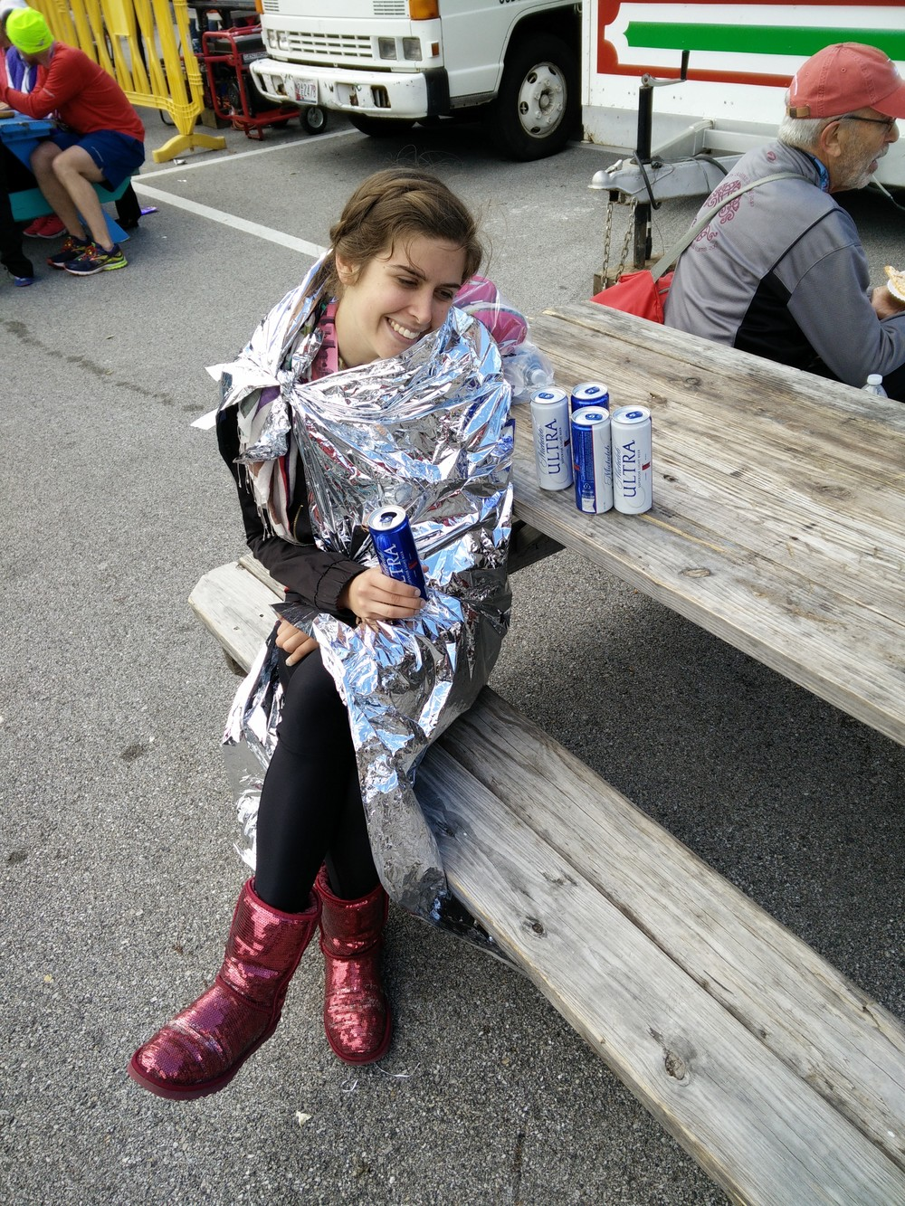Alana chillaxin' with some free Michelob Ultra in a mylar cape and sparkly red Uggs after a PR finish.