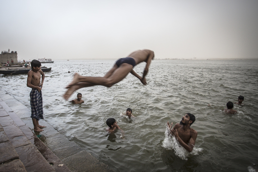 INDIA, Varanasi - a man jumps into the River Ganges.