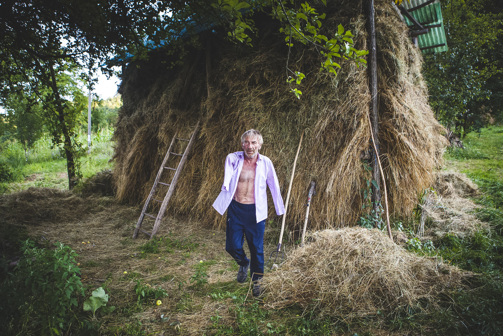 Istv�n Szuh�nyi outside his home in Transylvania - behind him is a large pile of hay that he adds to each day.