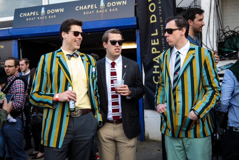 Spectators wearing boating blazers gather during the annual Boat Race between Oxford and Cambridge University along the River Thames in Putney on April 02, 2017 in London.