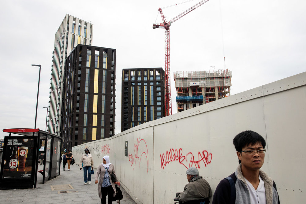 Cranes tower over a building development underway as people walk past a bus stop in Lewisham on August 22, 2017 in London.