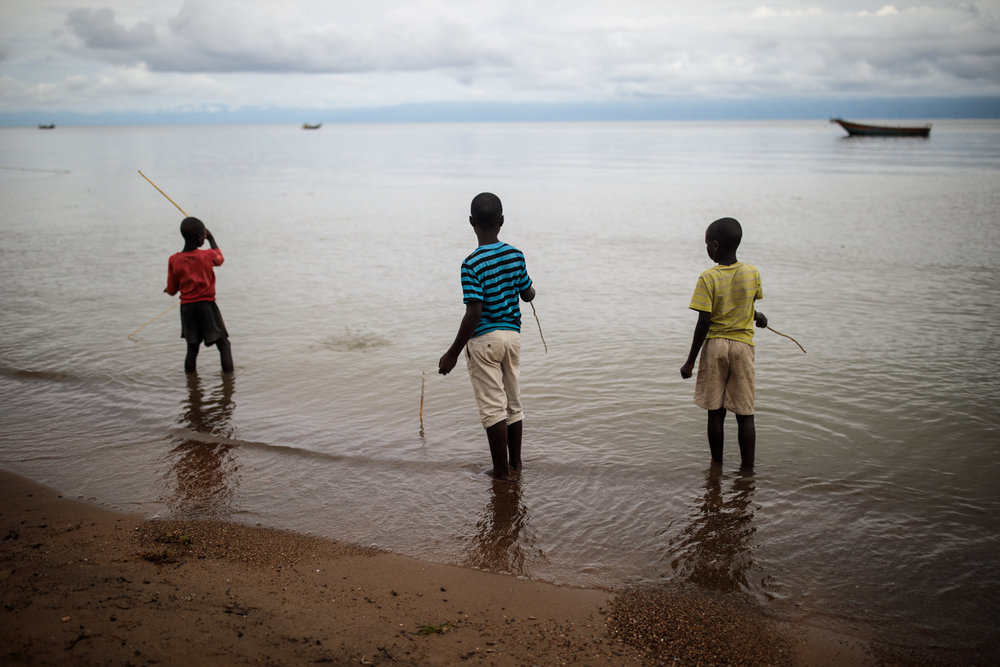Sebagoro, Uganda - Children play with home-made fishing rods on the banks of Lake Albert, 2018.