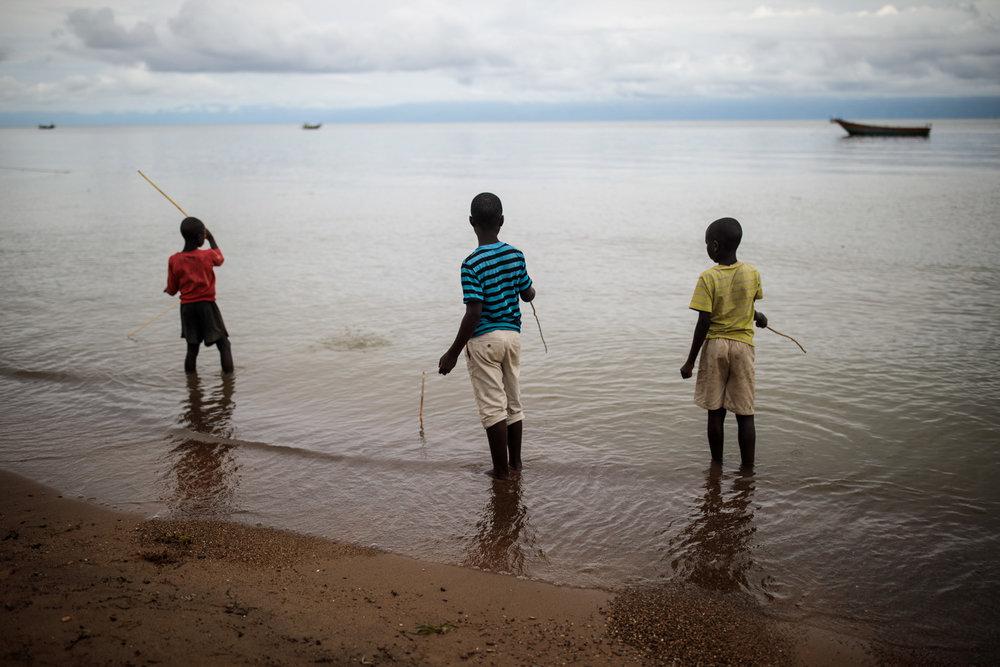 Sebagoro, Uganda - Children play with home-made fishing rods on the banks of Lake Albert, 2018.