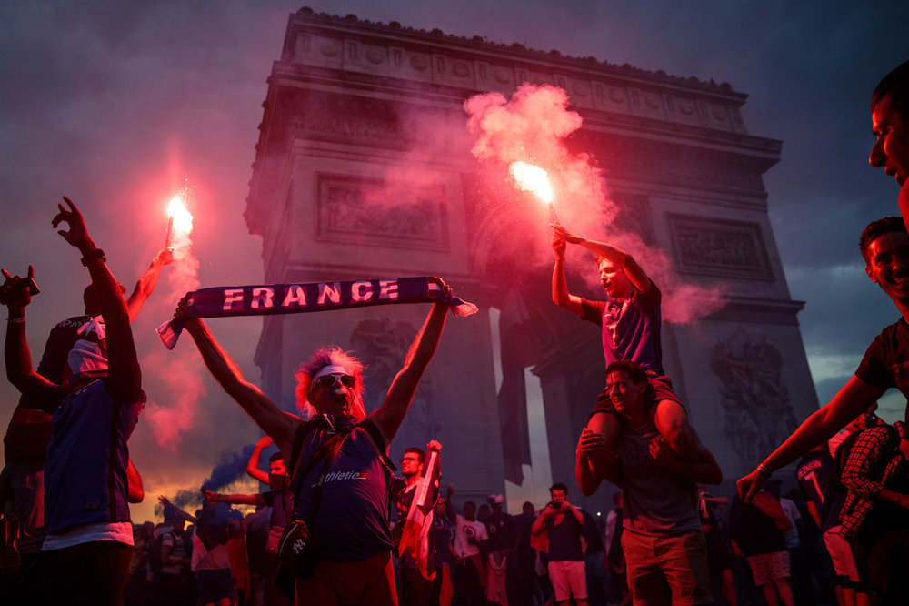 Paris, France - Football fans celebrate in front of the Arc de Triomph after France's victory against Croatia in the 2018 World Cup Final.
