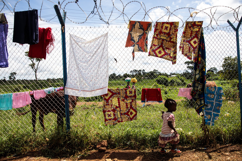 KYANGWALI, UGANDA: A young refugee from the Democratic Republic of Congo plays by a perimeter fence of the Kagoma reception centre on April 5, 2018.