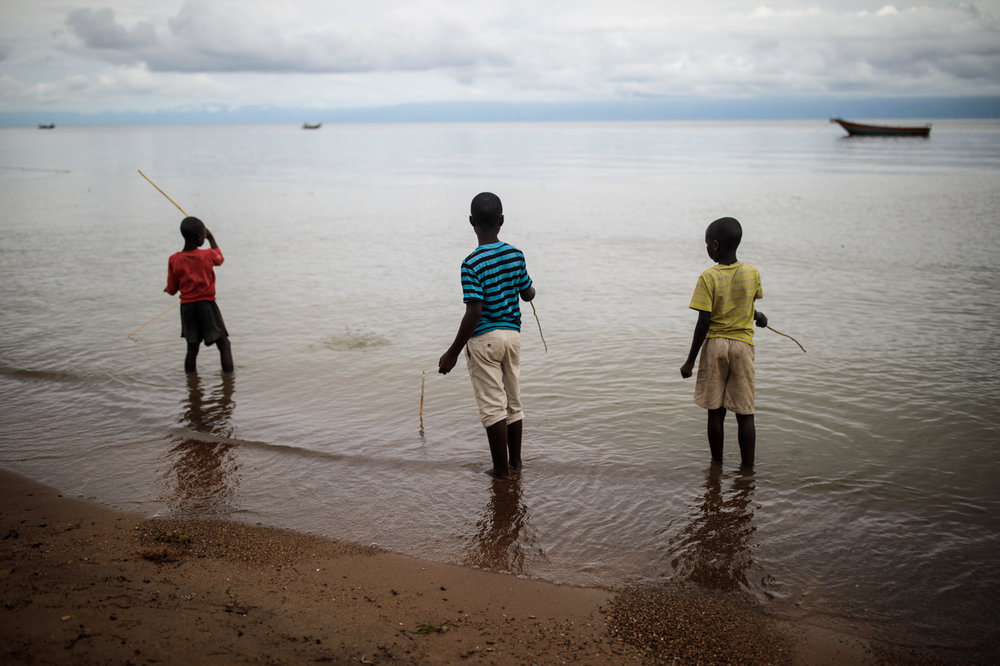 SEBAGORO, UGANDA: Local children play with home-made fishing rods on the banks of Lake Albert on April 4, 2018.