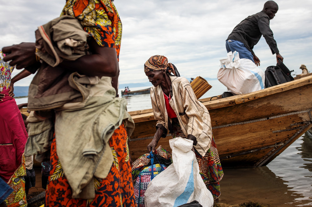 NSONGA, UGANDA: Refugees from Tchomia in the Democratic Republic of Congo gather their belongings as they arrive on boat at the Nsonga landing site on April 9, 2018.