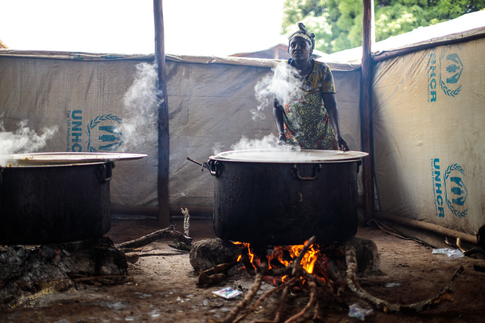 KYANGWALI, UGANDA: A volunteer helps cook food from the World Food Programme for refugees from the Democratic Republic of Congo in the Kagoma reception centre within the Kyangwali settlement on April 10, 2018.