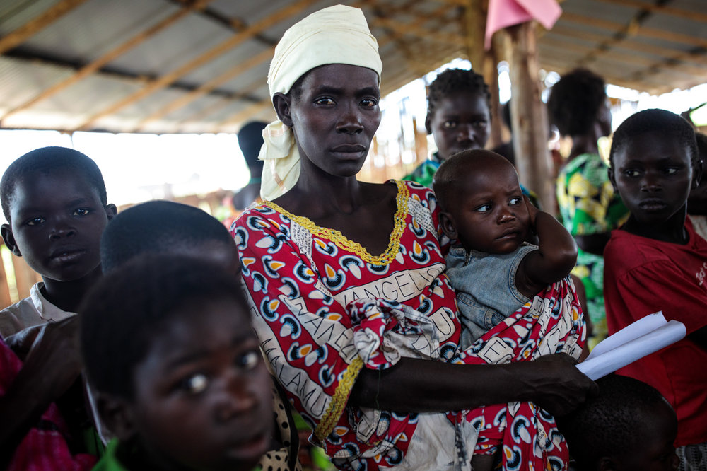 KYANGWALI, UGANDA: Refugees from the Democratic Republic of Congo wait with their children to be screened for malnourishment in the Kyangwali Refugee Settlement on April 6, 2018.