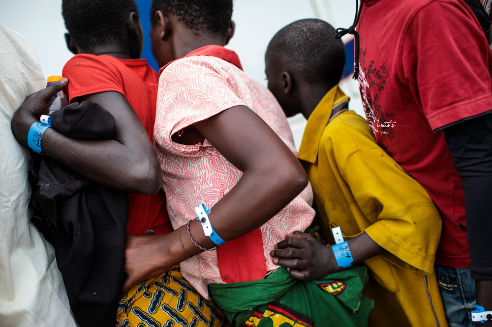 NSONGA, UGANDA: Refugees from the Democratic Republic of Congo, wearing registration wristbands, prepare to board a bus from the Nsonga landing site to a reception centre on April 9, 2018.