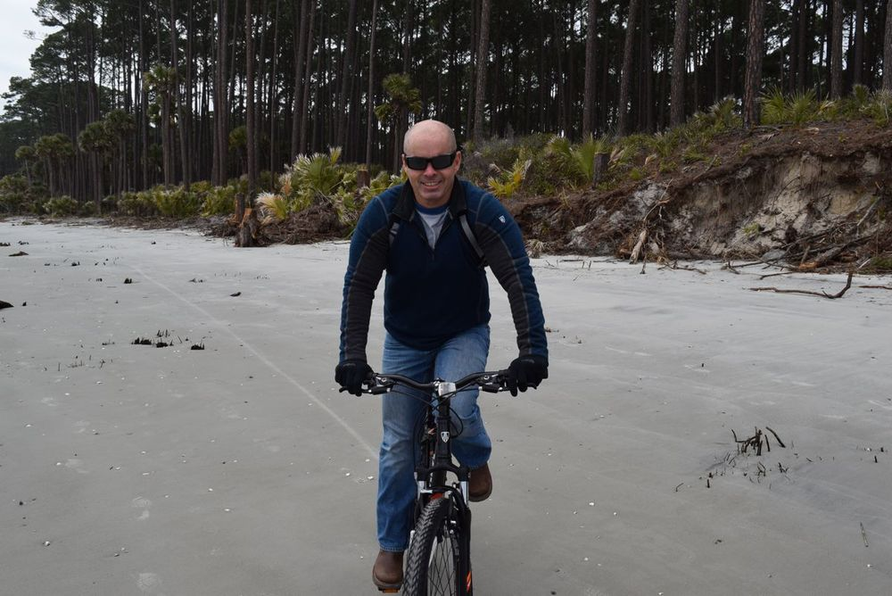 Paul riding his bike on the beach.