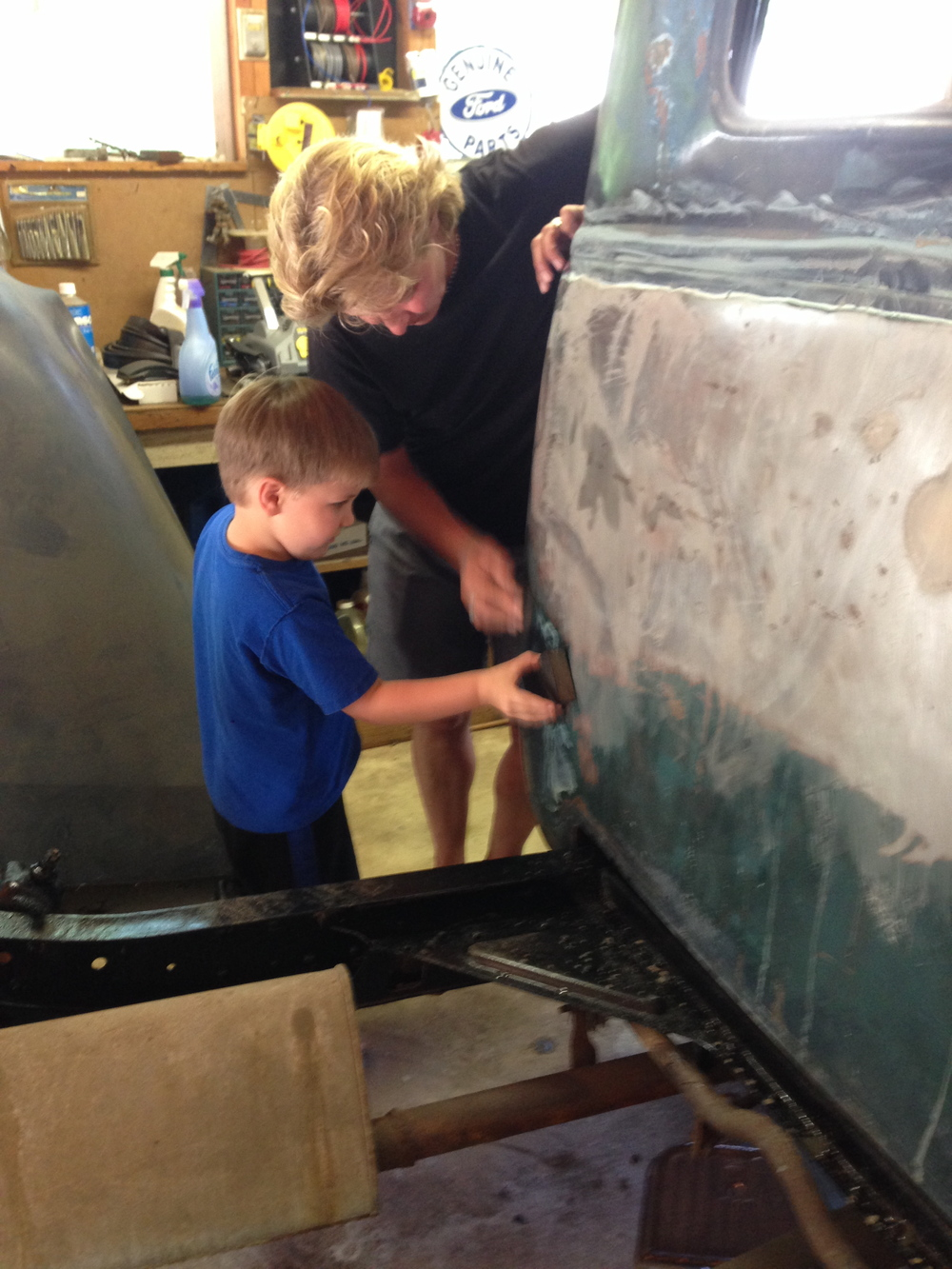 Annie, teaching Bentley how to sand the truck.