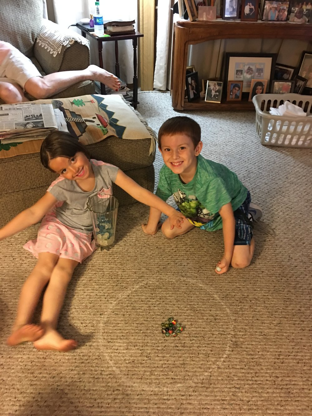 The little one's in the family always make sad times a lot better! Teaching my great nephew and niece how to play marbles.