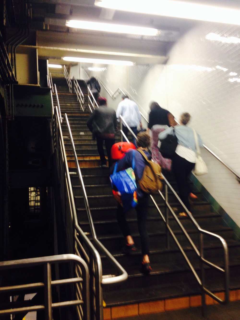 A precarious climb up the subway steps, bags in hand.