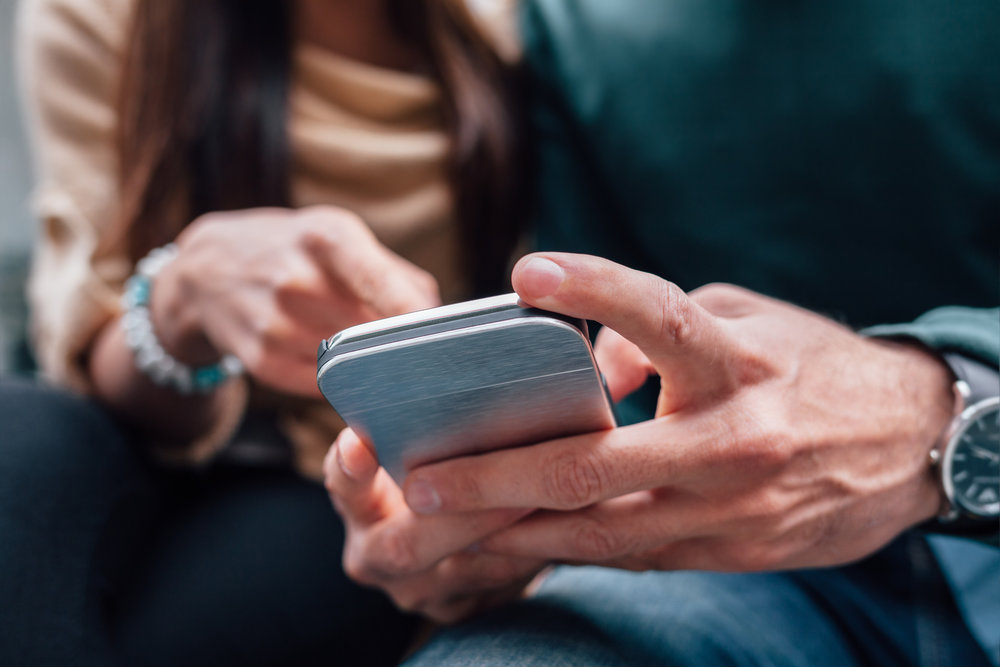couple looking at phone - property management tech trends 2018