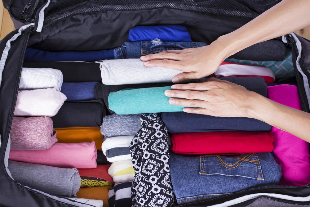 packed suitcase - real estate agent moving guide