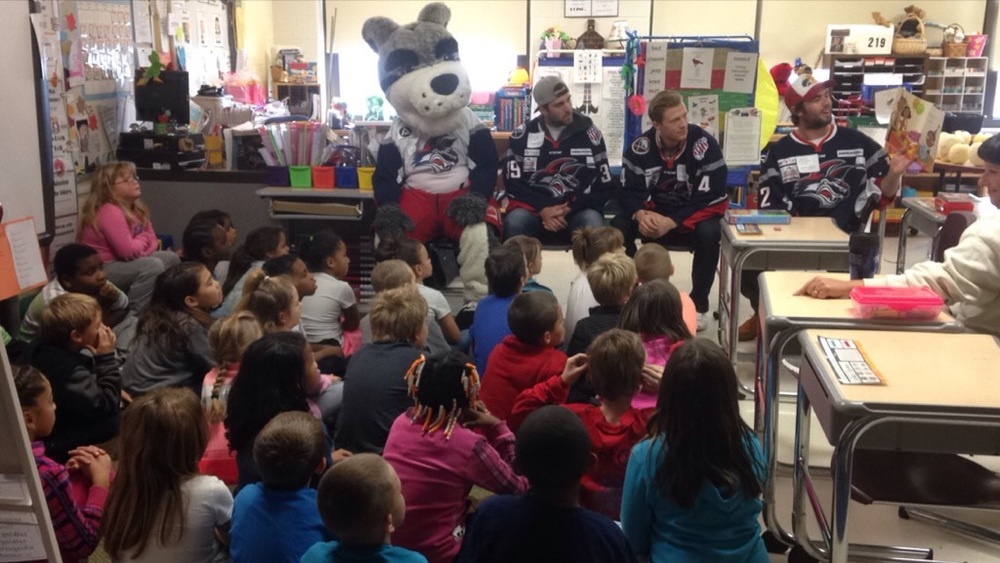 Jackals Forward Scott Jacklin reads to Fassett Elementary students as, Zach Tolkinen, Sam Marotta, and Blade look on.