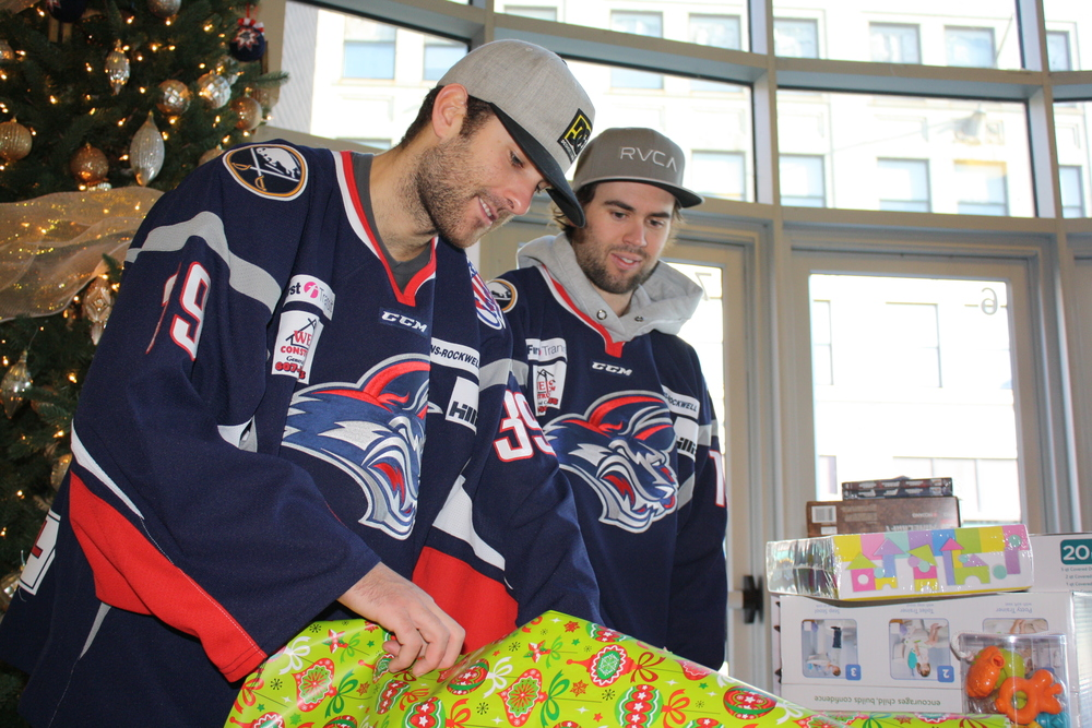 Former Jackals standouts, Goaltender Sam Marotta (left) and Forward Scott Jacklin (right), wrap presents for Christmas families. Marotta is now with the Rapid City Rush in Rapid City, SD, and Jacklin with the Brampton Beast in Brampton, ON, CA.