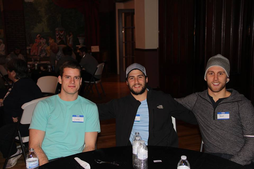 Left to right: Jacob MacDonald, Mike Seidel, and Mark Bennett pose for the camera and the Holiday Party