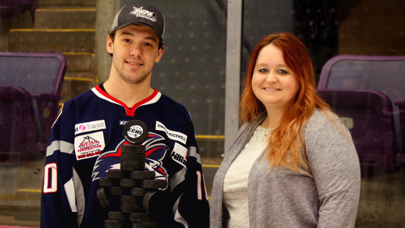 Cason Hohmann presents Elmira Jackals Youth Hockey representative Lynn Bassler with a case of pucks from Sher-Wood Hockey.