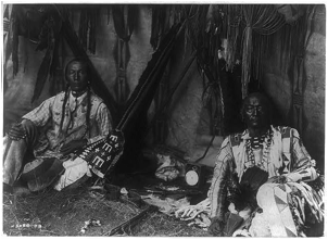 Photographic print by Edward Curtis of Little Plume and his son, c1910, with the clock they own and use between them