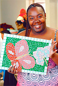 Shannell Harvey shows off a glass butterfly mosaic that she created. Piece by Piece is a nonprofit that teaches the homeless of Skid Row and South L.A. to create beautiful mosaic artwork. Los Angeles, CA 6/4/2010. photo by John McCoy