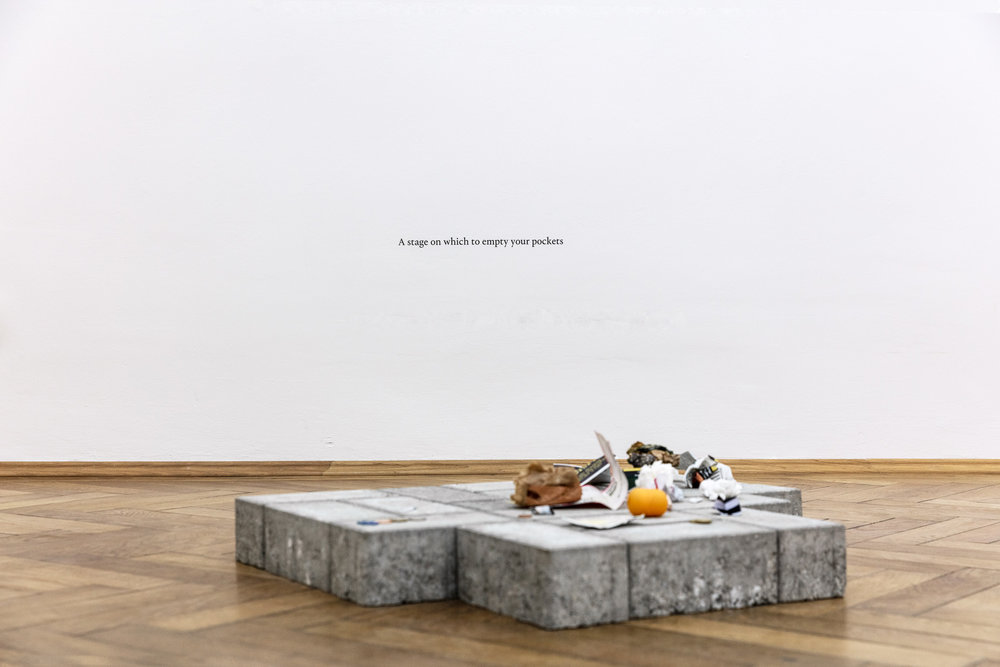 Thomas Geiger, A stage on which to empty your pockets, 2017, concrete pavement tiles, adhesive letters, 60 x 70 x 80 cm