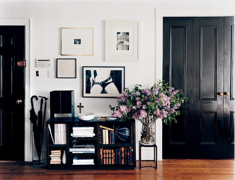 Looking to make a bold statement? Give your doors a makeover with glossy  dark paint. The moody hue will add contrast and sophistication to a neutral space. Via  Domino