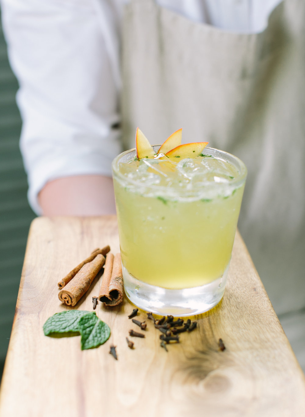 Front Porch Cooler - Glass – large rocks/old fashionedMethod – shake and strainGarnish – slapped mint sprig; thin peach slices2 oz. bourbon whiskey.75 oz. velvet falernum liqueur1 oz. fresh lemon juice.5 oz. bar syrup3 healthy dashes peach bitters8 mint leaves