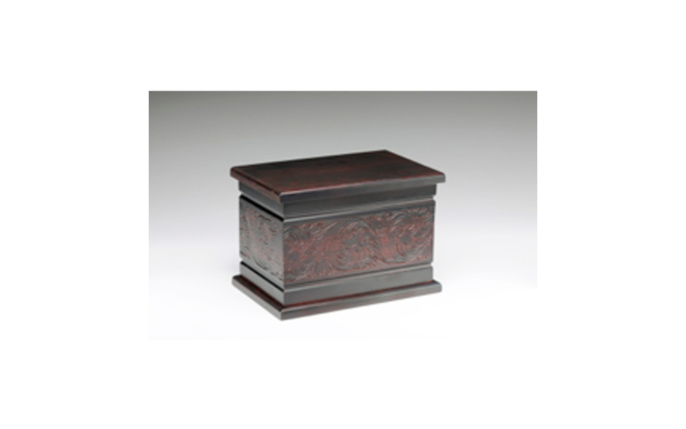"Northwoods Estonian Pine Dark Cherry This urn is made of solid pine and is stained with a dark cherry finish. This urn has a beautiful carved design. It opens at the base with a 3"" wooden plug which securely screws in place.  Measures 11"" L x 7.25"" W x 7.5"" H, 300 Cu. Inches, up to 295 lbs., $175"