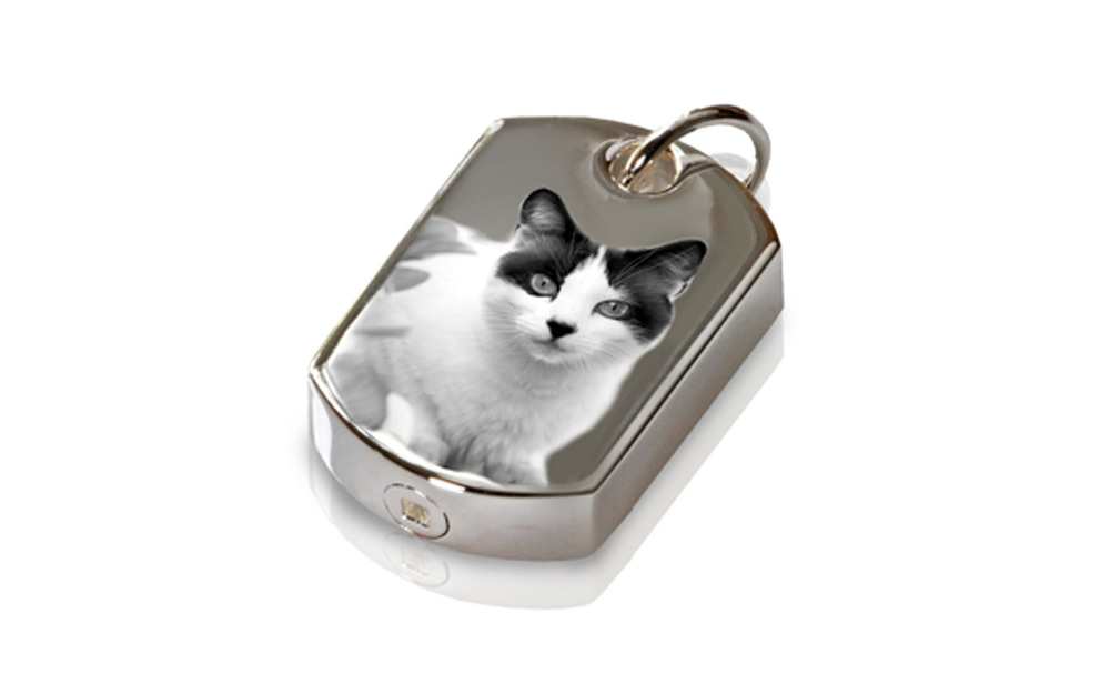 "Photo Engraved Dog Tag   This Stainless Steel pendant laser engraved with the photo of your choice is designed to hold cremated remains or fur clippings of your beloved pet. It measures 7/8"" H x 5/8""W.  Cost of back engraving is not included.    $245"