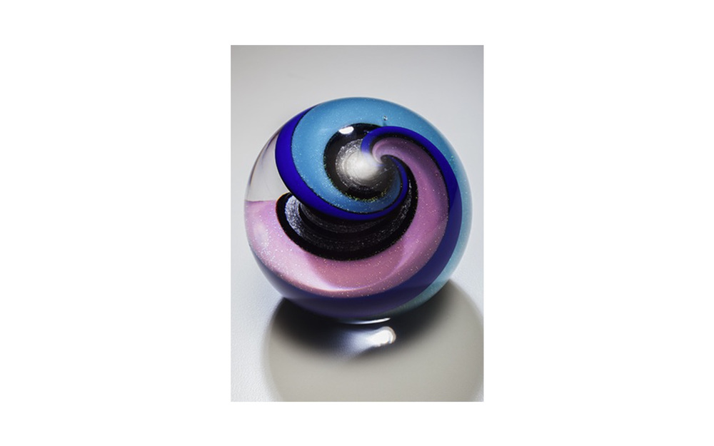 "Celestial Spring Spiral   This perfectly round marble is 3 1/4"" in diameter available in three special colors. The iridescent glass twists inside with the cremated remains to give it a Celestial feeling. This piece is truly a marble, so included is a marble ring for standing.    $415"