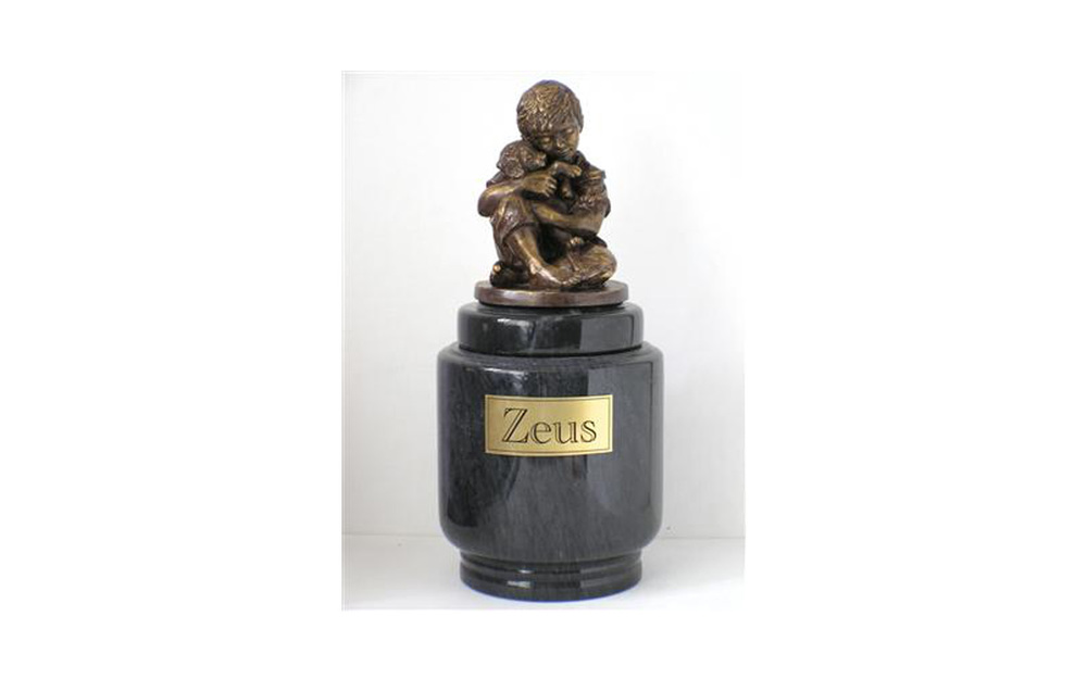 Friends Forever This beautiful genuine marble urn holds a figurine made of cold cast bronze (polymer with bronze additive). The figurine is available with a boy holding a dog or a girl holding a dog or cat.  Small measures: 50 Cu. Inches, up to 50 lbs. $275 without name plate $300 with name plate Large measures: 90 Cu. Inches, up to 90 lbs. $295 without name plate $320 with name plate