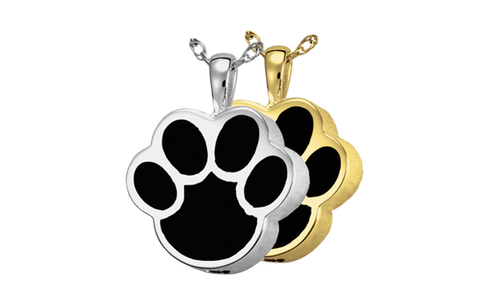 "Paw Shaped Urn Pendant with Black Inlay This pendant measures 7/8""H x 6/8""W (including the bail) and comes in both Sterling Silver or Gold Plated. Has a threaded opening at the bottom to fill with ashes or hair of your beloved pet. Sterling Silver: $185 14K Gold Plated: $210"