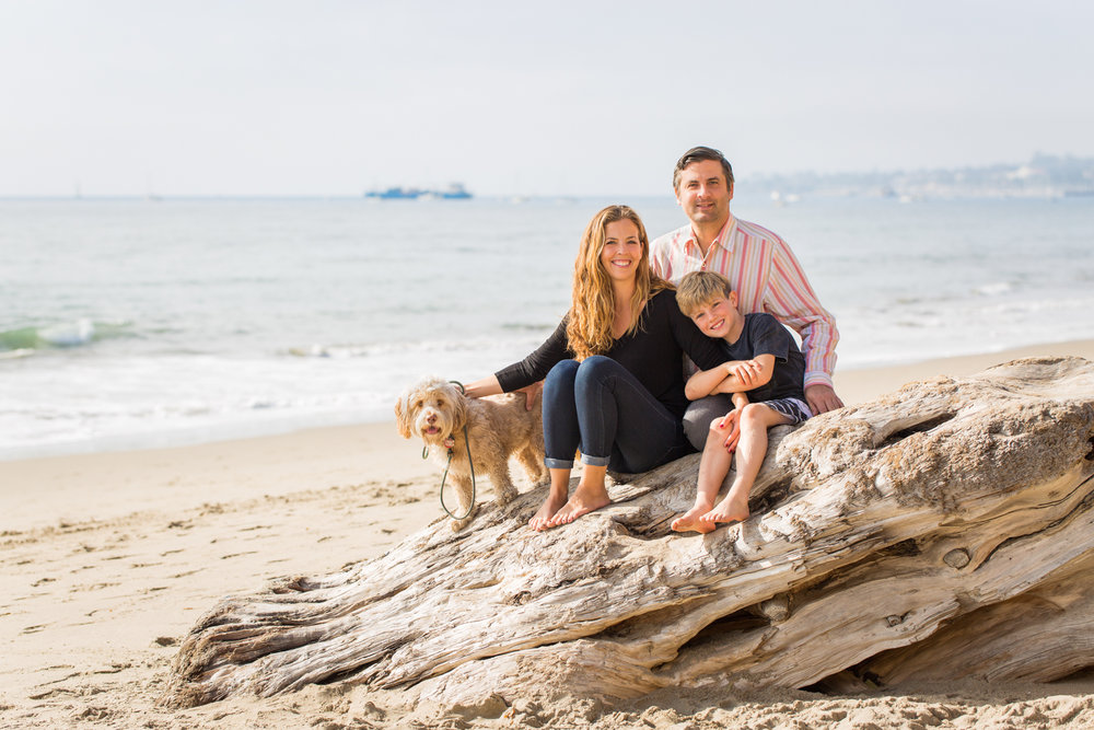Family portrait with their dog, sitting on a rock at Butterfly Beach in Santa Barbara.