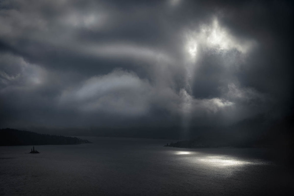 Sun breaks through the low hanging clouds to illuminate the lake below