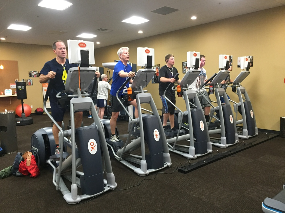 -Koko members Rick, Glenn, Tobi, and Trevor pushing each other through an elliptical HIIT program-
