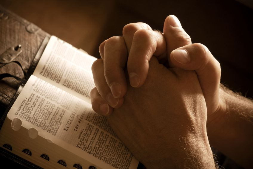 Praying hands with bible.