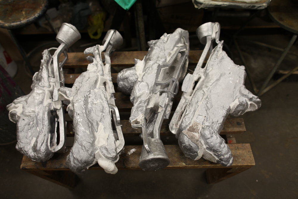 Aluminum cast snowmobiles (with sprues attached) are freed from their ceramic shells.